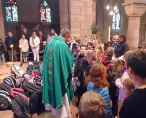 Père Nicolas au milieu des enfants et des cartables lors de la mese de rentrée du 17 septembre 2017